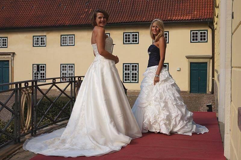 Zwei Modelle präsentieren Hochzeitskleider auf einer Messe