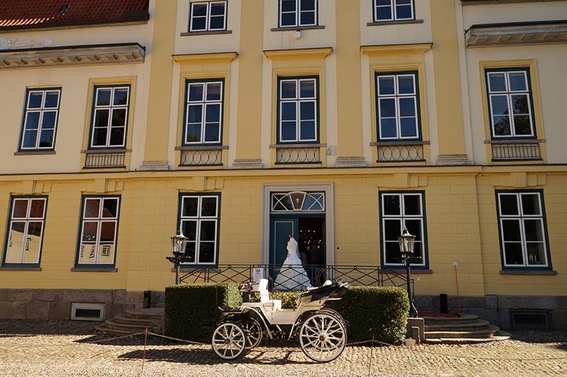 Eine Kutsche steht vor dem Eingang des Hauptgebäudes