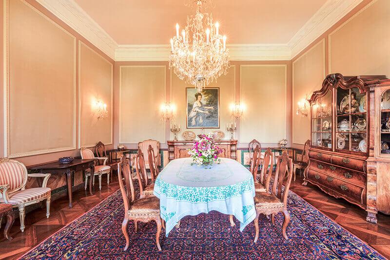 Großer Tisch unter einem Kronleuchter in einem herrlichen Ambiente