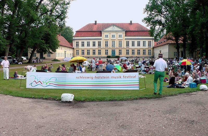 Menschen auf dem Vorplatz des Gut Emkendorf beim Musikfestival