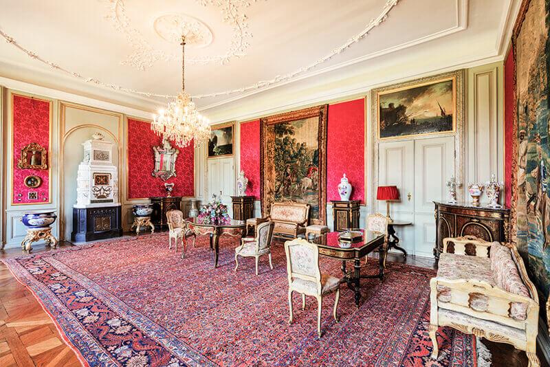 Salon mit roten, leuchtenden Wänden und stilvollen Möbeln