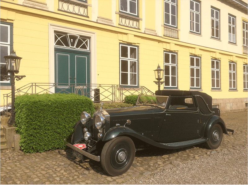 Ein Oldtimer steht vor dem Eingang des Herrenhauses