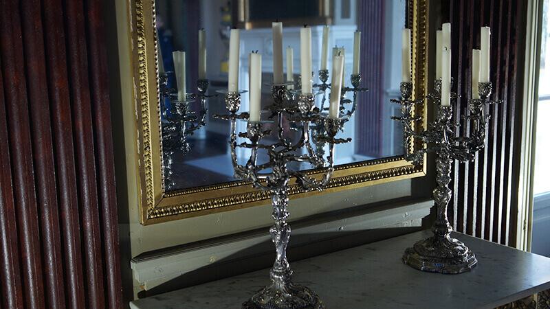 Zwei Kerzenleuchter stehen vor einem Spiegel