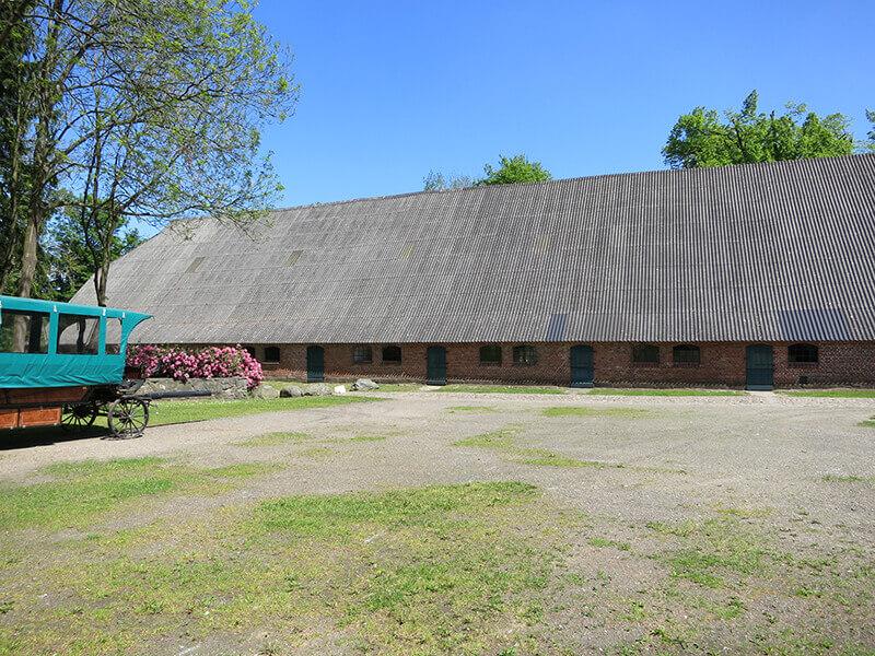 Das Kuhhaus von der Seite mit dem Vorplatz und einem Pferdeanhänger