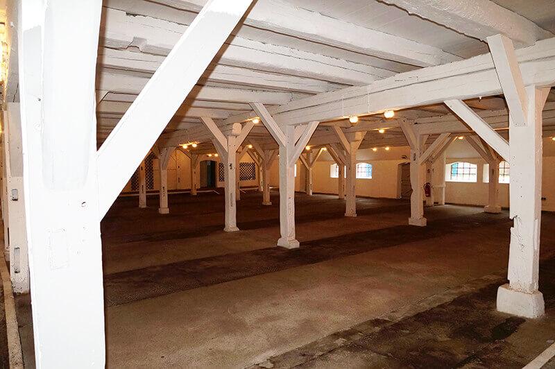 Das leere Kuhhaus von innen, weiße Balken und Decke
