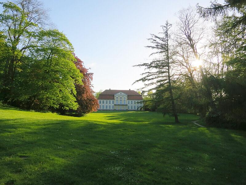 Blick auf die Rückseite des Herrenhauses aus dem Park